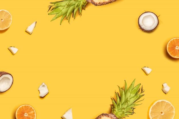 Composizione estiva creativa di frutti tropicali; arance, noci di cocco, limoni, ananas.