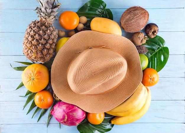 Composizione estiva foglie di palma tropicali, cappello, molti frutti su fondo di legno blu.