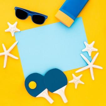 Composizione estiva stelle marine, occhiali da sole, cornice vuota blu su giallo pastello