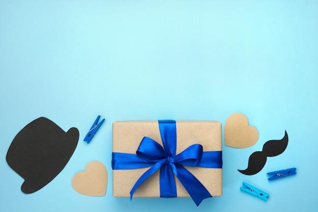 Composizione festa del papà. confezione regalo avvolto in carta artigianale con nastro blu, cuori, baffi, cappello nero e spille su sfondo blu.