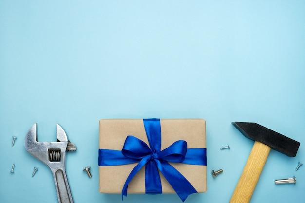 Composizione festa del papà. contenitore di regalo avvolto in carta kraft con l'arco del nastro blu e gli attrezzi per bricolage su fondo blu.