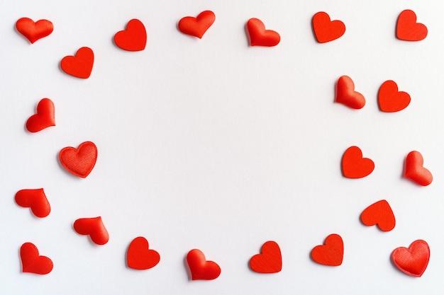 Composizione festiva da cuori rossi sparsi su bianco per san valentino