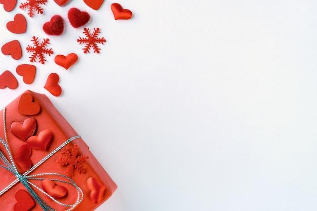 Composizione festiva da regalo rosso legato, fiocchi di neve e cuori sparsi su bianco per san valentino