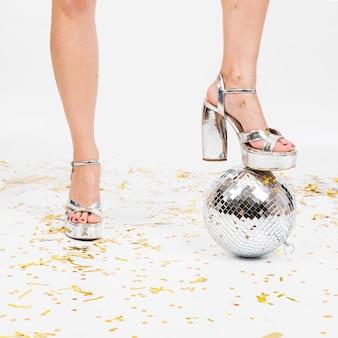 Composizione festosa di palla da discoteca e gambe