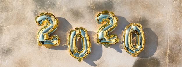 Composizione flat lay di capodanno. palloncini di alluminio sotto forma di numeri 2020.