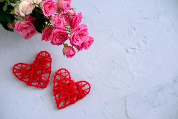 Composizione floreale con rose rosa e due cuori rossi su sfondo grigio. san valentino sullo sfondo. vista piana, vista dall'alto.