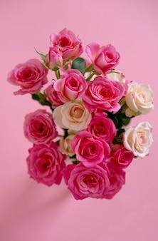 Composizione floreale con rose rosa su sfondo rosa. san valentino sullo sfondo. vista piana, vista dall'alto.