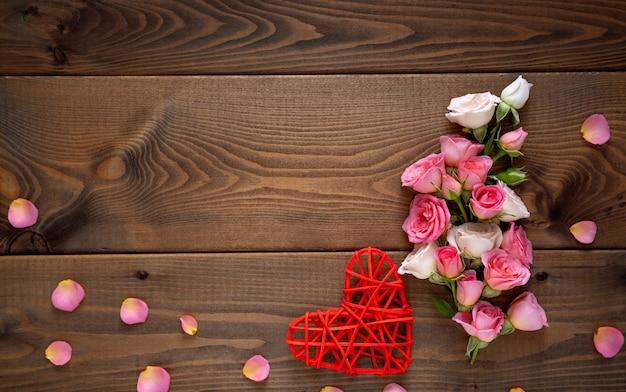 Composizione floreale con una corona di rose rosa e cuore rosso su fondo di legno. san valentino sullo sfondo. vista piana, vista dall'alto.