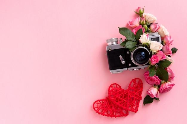 Composizione floreale con una corona di rose rosa e fotocamera su sfondo rosa. san valentino sullo sfondo. vista piana, vista dall'alto.