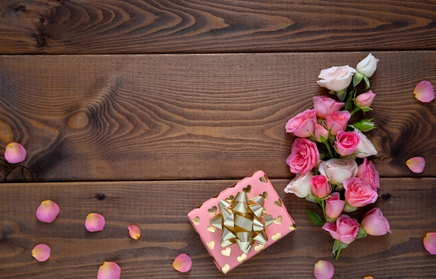Composizione floreale con una corona di rose rosa su fondo in legno. san valentino sullo sfondo.