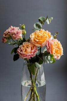 Composizione floreale di peonia e rose ad arbusto e rami di eucalipto.