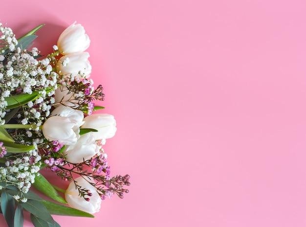 Composizione floreale di primavera su una parete rosa