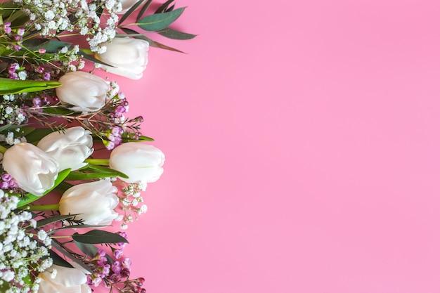Composizione floreale di primavera su uno sfondo rosa