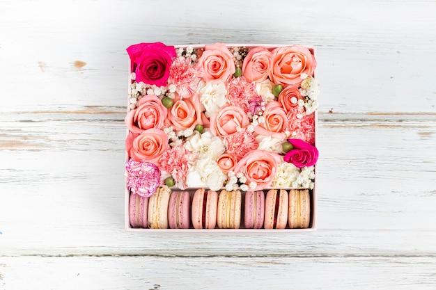 Composizione floreale di rose rosa con macarons di diversi colori