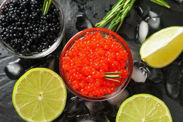 Composizione fresca con caviale e agrumi sul tavolo nero, da vicino