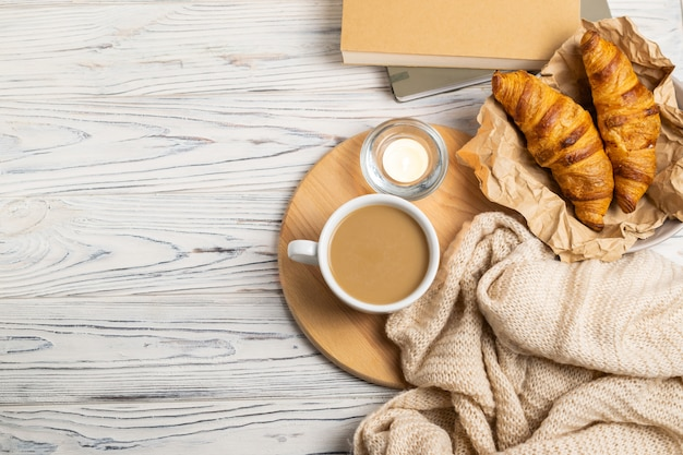 Composizione hygge con caffè, candele, cornetti freschi, quaderno per scrivere e plaid in maglia. posa piatta