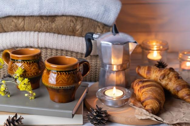 Composizione hygge con due tazze di argilla rustica, cornetti, libri, candele e maglieria sul tavolo di legno