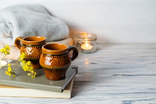 Composizione hygge con due tazze rustiche di tè, libri, candele e plaid in maglia