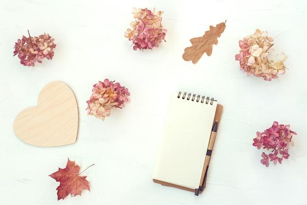 Composizione in autunno con il taccuino e fiori e foglie asciutti