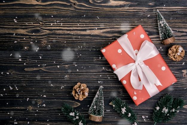 Composizione in festa di natale con decorazione rossa confezione regalo su fondo in legno