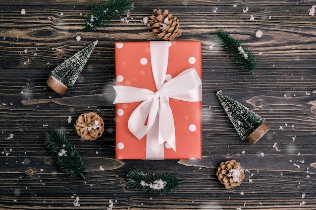 Composizione in festa di natale con il contenitore di regalo rosso e la decorazione dell'etichetta su fondo di legno