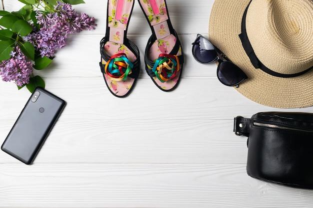 Composizione in moda bellezza con scarpe cappello occhiali da sole cellulare e fiori su bianco in legno