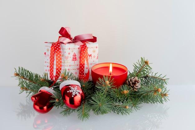 Composizione in natale con decorazioni, scatole regalo, candela rossa, guanti di babbo natale e palline su bianco. vacanze di natale con copyspace.