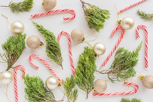 Composizione in natale con palline d'oro, rami di abete, bastoncini di zucchero su bianco. concetto di nuovo anno.