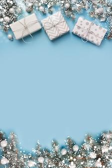 Composizione in natale con rami di abete e scatole regalo bianche