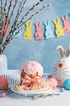 Composizione in pasqua con il dolce e le uova di pasqua sulla tavola di legno bianca contro la superficie del blu