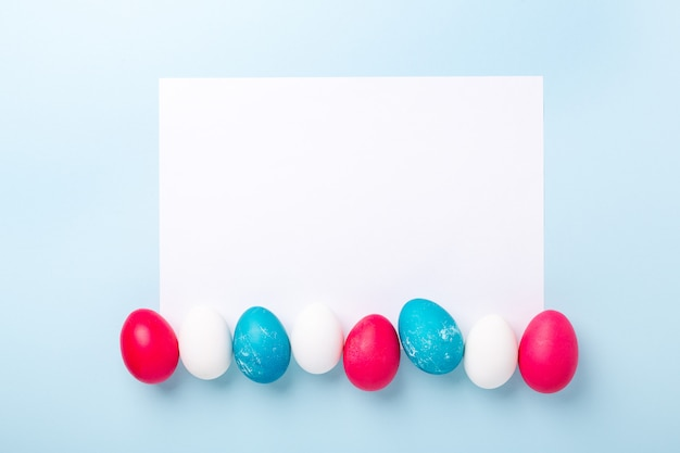 Composizione in pasqua con le uova e lo spazio in bianco di libro bianco su fondo blu. concetto di pasqua. copia spazio. vista dall'alto
