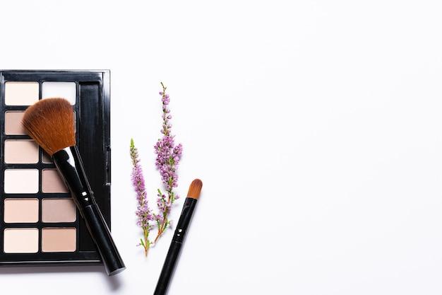 Composizione in stile minimalista con tavolozza cosmetica, pennelli cosmetici e ramoscelli di fiori su sfondo bianco.