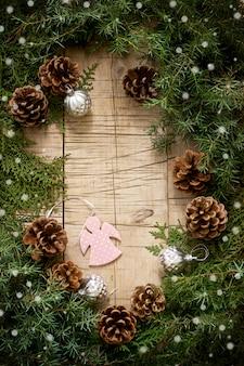 Composizione invernale con rami di ginepro e thuja e giocattoli di natale su un fondo di legno. stile rustico.