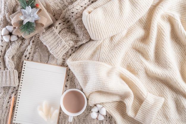 Composizione invernale con tazza di caffè e blocco note