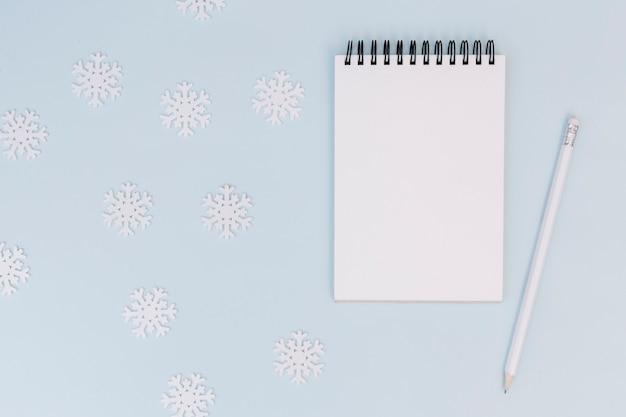 Composizione invernale del blocco note con fiocchi di neve