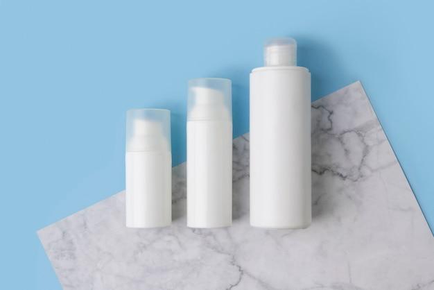 Composizione minima con flaconi per la cosmetica sul tavolo blu e marmo creativo