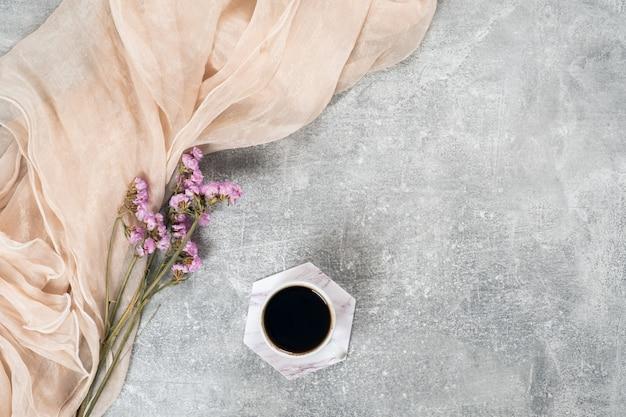 Composizione minimale laica piatta con sciarpa, tazza di caffè, fiori secchi rosa sulla superficie del calcestruzzo.
