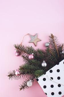 Composizione minimale piatta laica natalizia con rami di abete, sfere lucide di natale, stella in legno in sacchetto regalo a pois