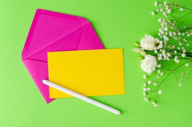 Composizione minimalista con una busta rosa, carta bianca gialla, penna e fiori. flay lay, mockup concept.