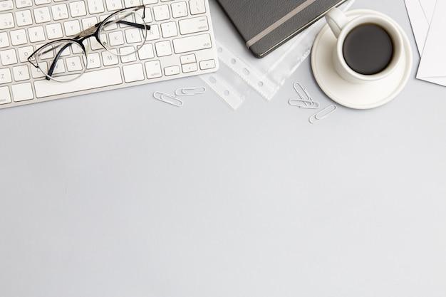 Composizione moderna sul posto di lavoro su fondo grigio con lo spazio della copia