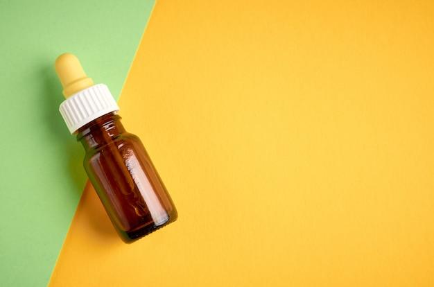 Composizione nasale nella bottiglia di gocce, bottiglia di vetro su fondo giallo e verde con copyspace