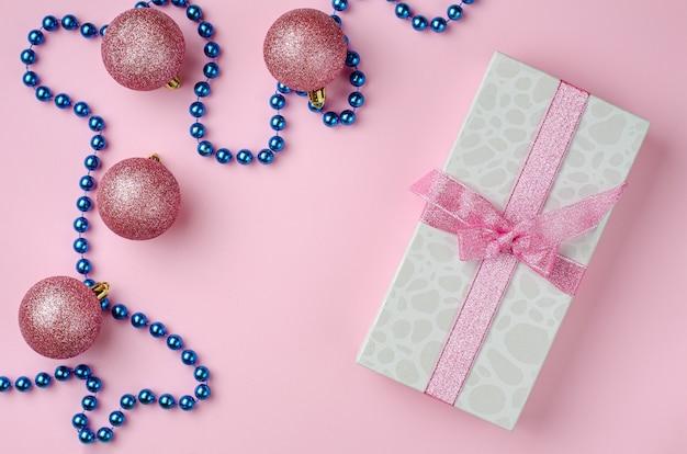 Composizione natalizia. confezione regalo con nastro e bagattelle su sfondo rosa