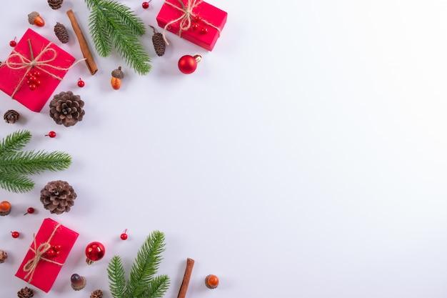 Composizione natalizia. contenitore di regalo, rami di abete e decorazioni su bianco