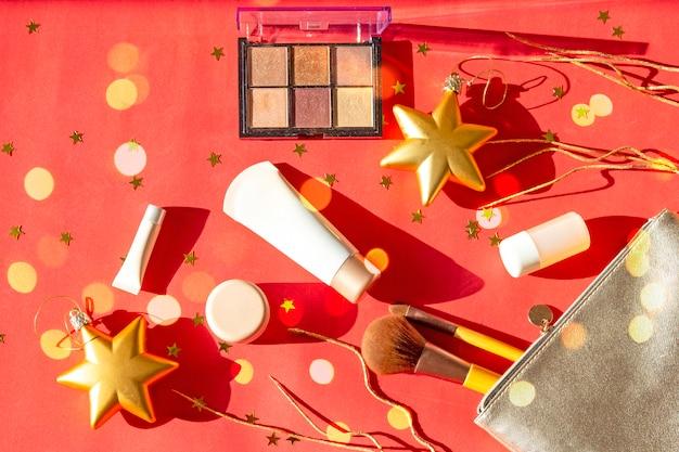 Composizione natalizia di accessori femminili per il trucco: ombretti, pennelli per il viso, creme e lozioni per il nuovo anno