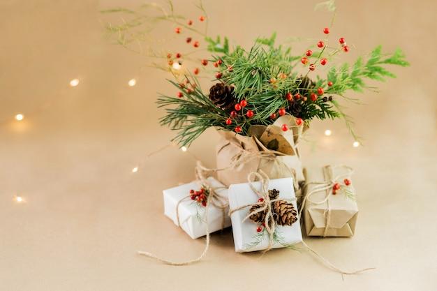 Composizione natalizia di materiali naturali. regalo di natale avvolto, coperta lavorata a maglia, pigne, rami di abete. vista piana, vista dall'alto