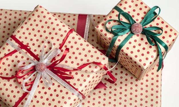 Composizione natalizia di varie scatole regalo avvolte in carta artigianale e decorate con nastri di raso. vista dall'alto, piatto.