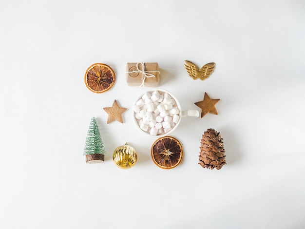 Composizione natalizia piatta: biscotto stellato, regalo, fette d'arancia secche, tazza con bevanda calda e marshmallow, pigna e abete di natale