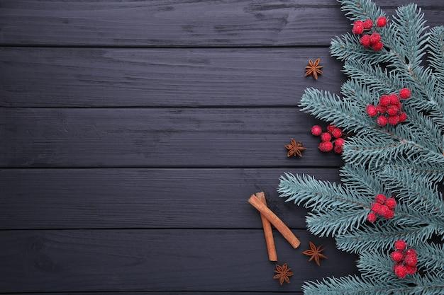 Composizione natalizia. rami di abete e bacche di viburno su uno sfondo nero