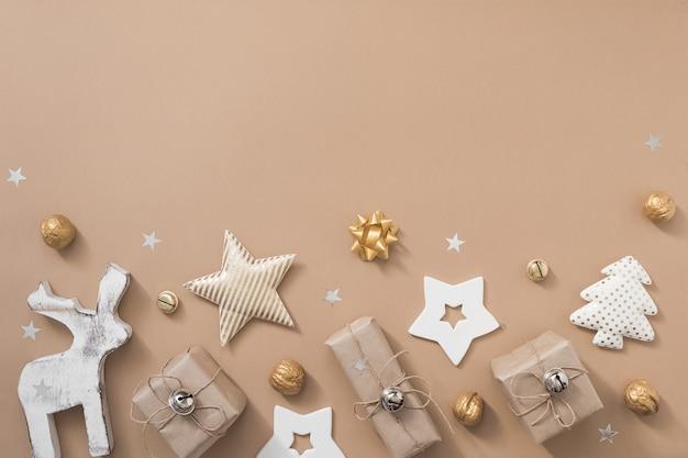 Composizione natalizia. regali, artigianato e decorazioni dorate su sfondo bianco. vista piana, vista dall'alto, copia spazio