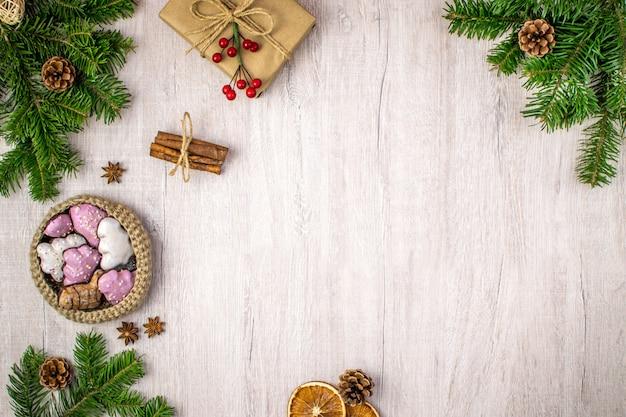 Composizione natalizia su legno per i saluti delle vacanze invernali. regalo di natale, cestino di pan di zenzero, stelle di anice, pigne, bastoncini di cannella, vischio su un legno strutturato.